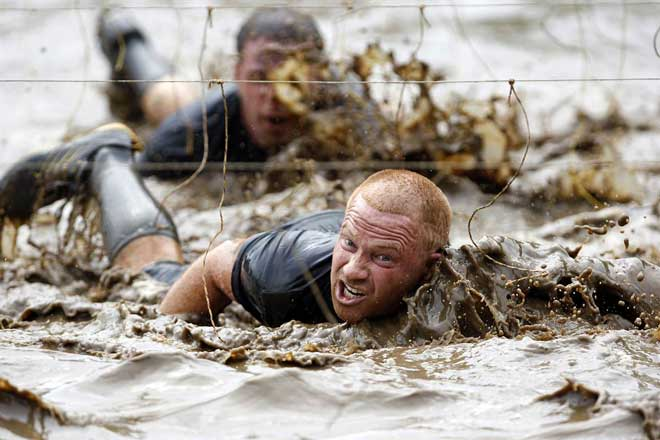 swim through mud underneath electrified wires during the Tough Mudder at Mt. Snow in West Dover Vermont on Sunday July 15. The Tough Mudder is a 9 mile endurance event The best sports photos of the week   Tough Mudder, Championship Hurdlers, Chinese Gymnastic schools for kids